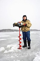 Man Drilling Ice Fishing Hole