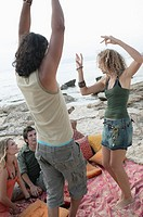 Young couple dancing on the beach with another young couple looking at them