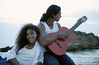 Young man playing the guitar with a young woman leaning against him