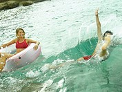 High angle view of a young man swimming with a young woman floating on a life belt