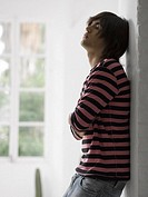 Side profile of a young man leaning against a wall