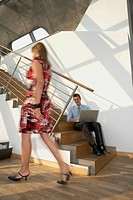 Businessman sitting on a staircase and using a laptop while young woman passing by him