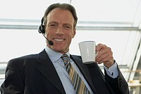 Close-up of a businessman wearing headset and holding a cup of tea