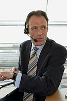 Close-up of a businessman wearing headset and checking the time