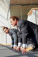 Side profile of two businessmen crouching at a starting line