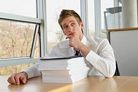 Businessman sitting with a stack of documents and looking worried