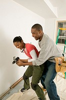 Male carpenter wrestling power drill away from girlfriend