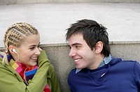 Smiling young couple fact to face, woman with earphones