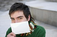 Young man covering mouth with a sheet of paper