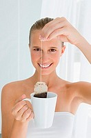 Young woman holding tea bag