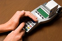 Person entering pin into card reader