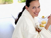 Woman in robe eating healthy breakfast outdoors