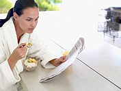 Woman in robe eating healthy breakfast outdoors (thumbnail)