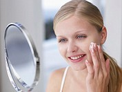 Woman applying lotion or cream to face in mirror
