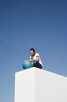 Man on block outdoors holding globe