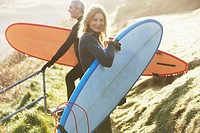 A man and a woman with surfboards