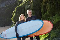 A man and a woman holding surfboards on the beach