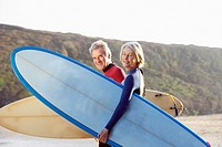 A man and a woman on the beach with surfboards