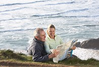 couple sitting outdoors reading a map