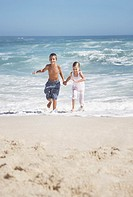 two young children running out of the water at the beach