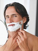 Closeup of man shaving with mirror
