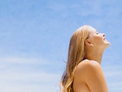 Side profile of woman outdoors with blue sky