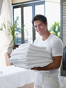 Man with a pile of towels in his arms