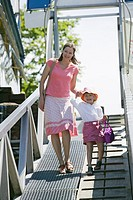 Caucasian Mom and 4 year old Daughter, walking down a ramp to a boat dock, Granville Island, Vancouver, B C