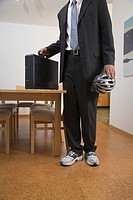 Young Man on the way to work wearing suit and sneakers holds helmet and briefcase