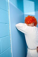 Man posing in his long underware and an orange wig