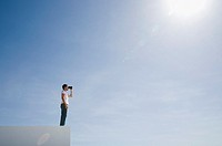 Man on pedestal with binoculars and blue sky outdoors (thumbnail)