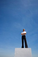 Businesswoman standing on pedestal outdoors