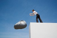 Businesswoman tossing beanbag chair off wall outdoors (thumbnail)