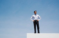 Businessman standing on wall outdoors with blue sky