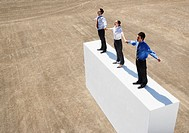 Three businesspeople standing on wall outdoors holding hands