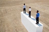 Three businesspeople standing on wall outdoors