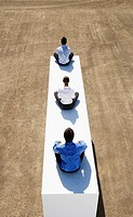 Three businesspeople sitting cross legged on wall outdoors (thumbnail)