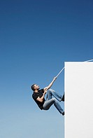 Man climbing wall with rope outdoors with blue sky