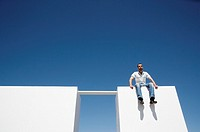 Man sitting on wall with board to other wall outdoors with blue sky
