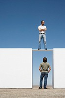 Man standing on board between two walls outdoors with man below