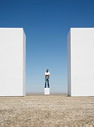 Man standing on box between two walls outdoors