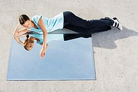 Woman lying down on ground with mirror and reflection (thumbnail)
