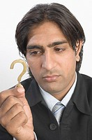 Close-up of a businessman holding a question mark sign