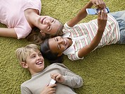 Three young kids two with cellular phones