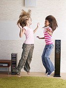 Two young girls playfully jumping around