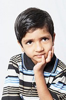 Close-up of a boy contemplating with his hand on his chin