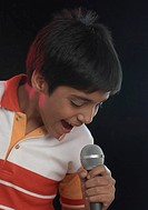 Close-up of a boy singing in front of a microphone