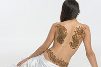 Rear view of a young woman with a tattoo on her back