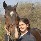 Portrait of a teenage girl standing with a horse and smiling