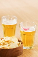 Close-up of beer glasses and a bowl of potato chips